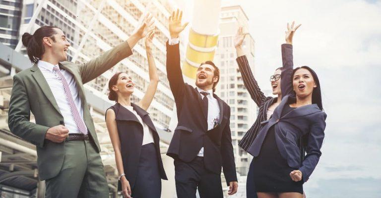 4 successful individuals raising their hands high.