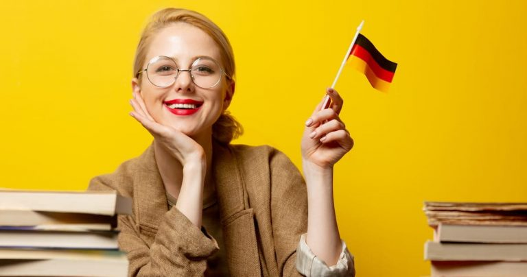Smiling woman holding the German flag with books around her.
