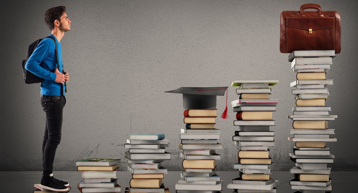 Young man with towers of books in front of him, topped off by a graduate's cap and a bag.