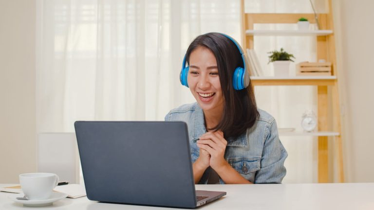 Girl smiling at her laptop during online training.