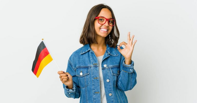 Young lady standing with the German flag in one hand and an 'O.K' sign