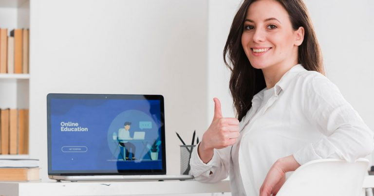 Woman taking an online English course in front of a computer screen with a thumbs up.