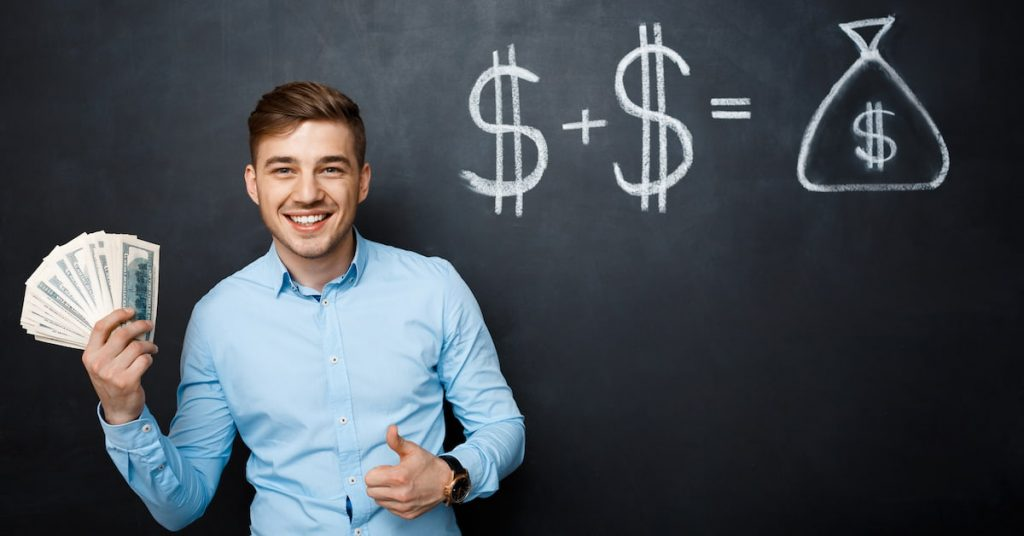 Man standing with money in his hand and a blackboard with money signs behind him.
