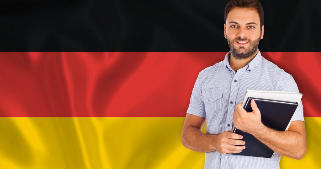 Man standing in front of the German flag with a book in hand.
