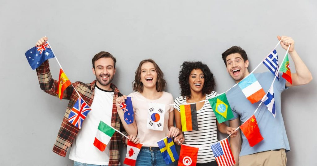 4 young men holding a string with different counties flags attached to it.