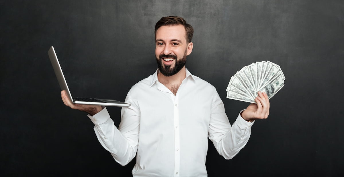 Man standing with a laptop in one hand and money in the other.