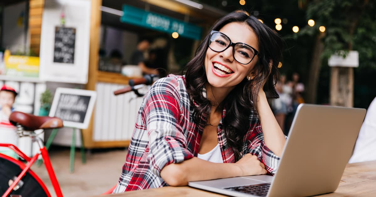 Smiling young lady sitting in front of laptop.
