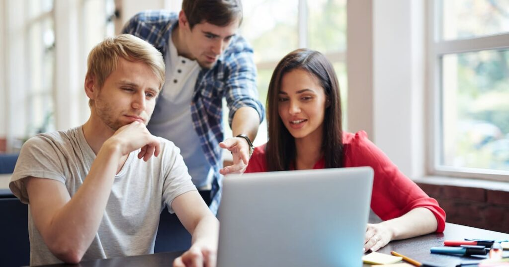 3 young people gathered around a laptop