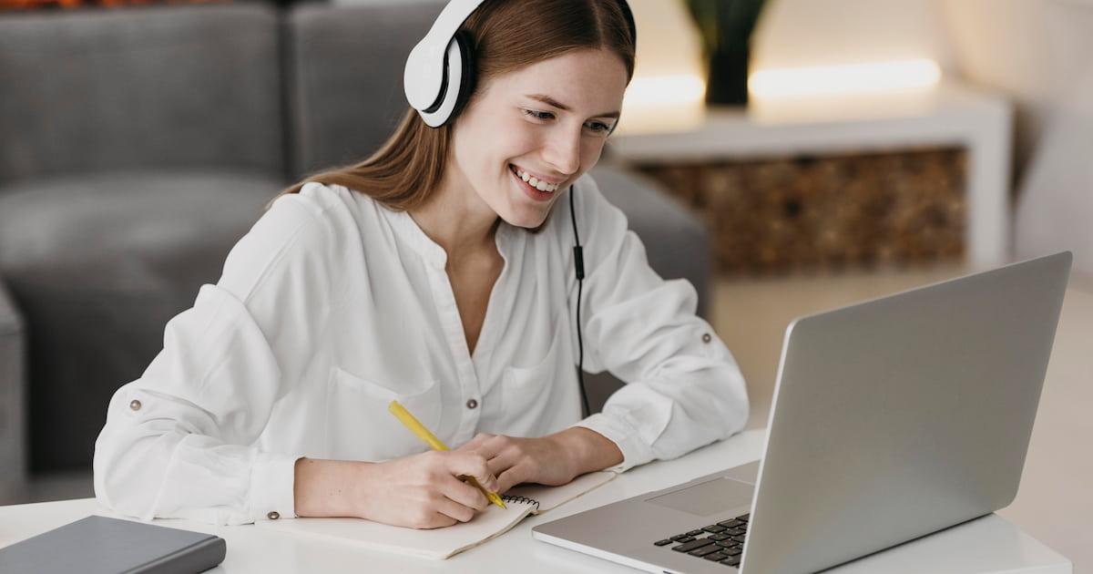 Young woman smiling at laptop during an online English course