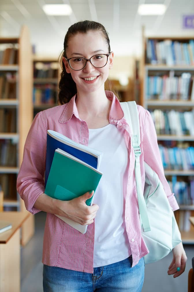 A Student Holding Notebooks And Smiling