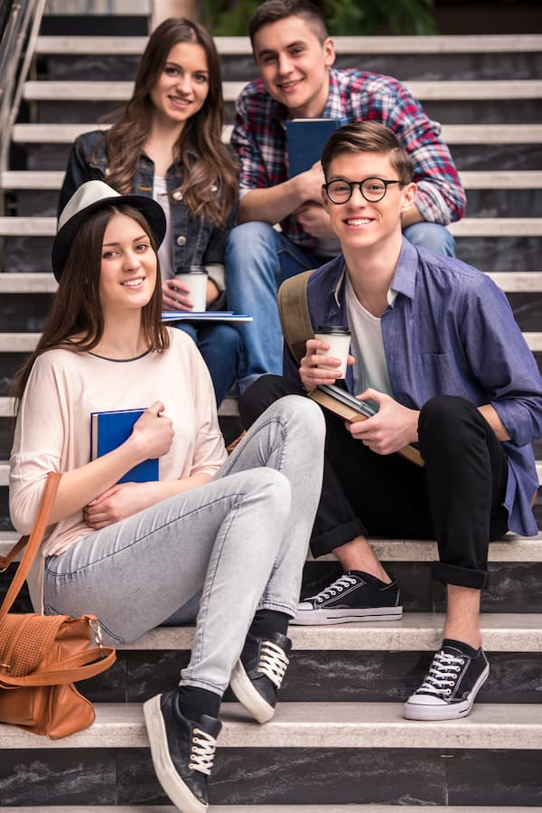 4 Students Sitting On The Stairs And Smiling
