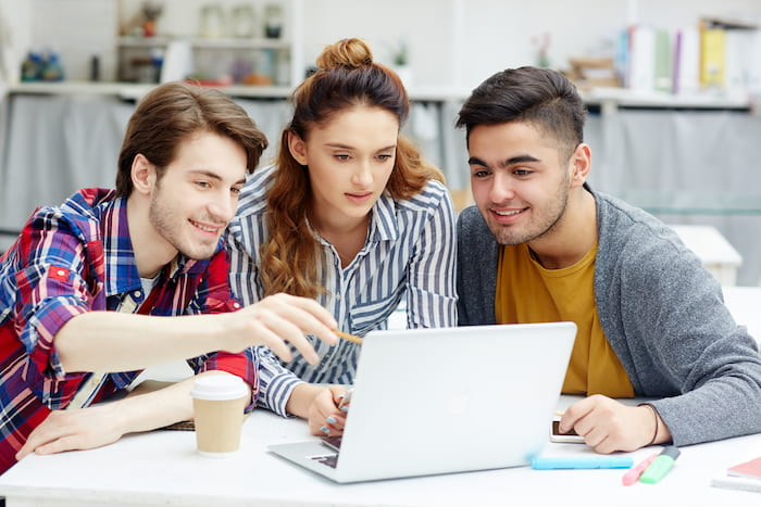 3 Students With A Laptop In Front Of Them