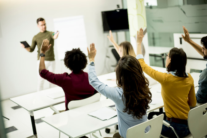 A Teacher Standing While Adult Students Are Raising Their Hands